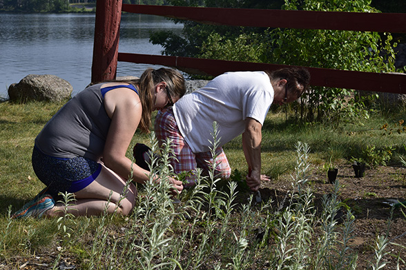 Two IAS participants kneel to plant plants in lakeside garden in Lac du Flambeau, Wisconsin