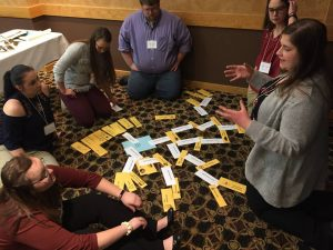 """Teacher participants at MN Ag-Tech conference kneel on floor around """"More or Less"""" activity cards describing potential benefits of habitat restoration"""
