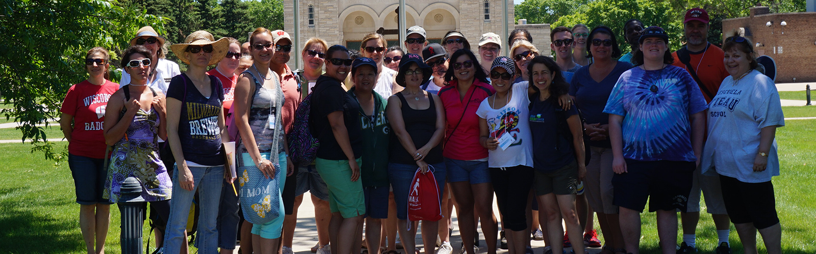 Group of participants in Latino Earth Partnership summer institute stand together in front of local church