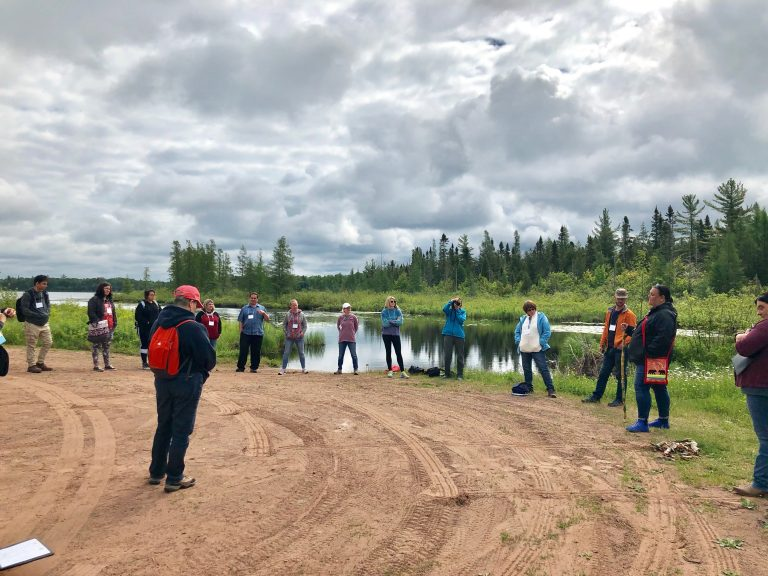 Participants gathered on gravel road listening to speaker, with water and woods in background