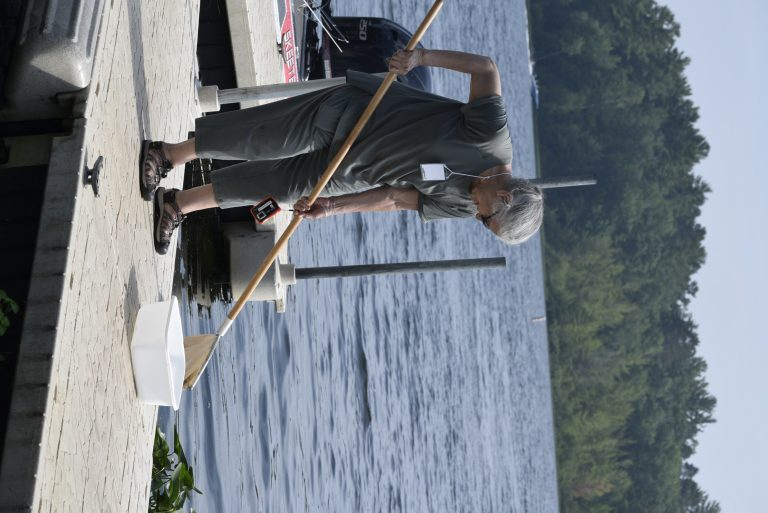 Woman stands on dock with long handled net, dipping into water below