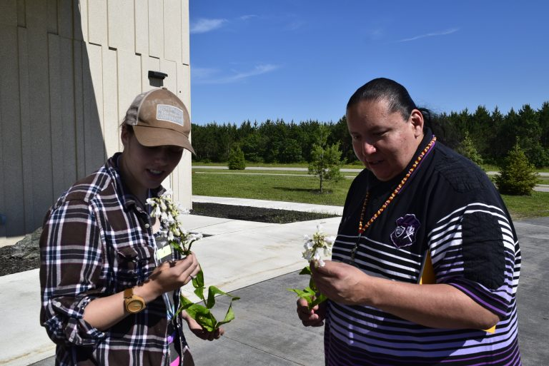 Two people stand outside, each examining a sample of the same prairie plants species
