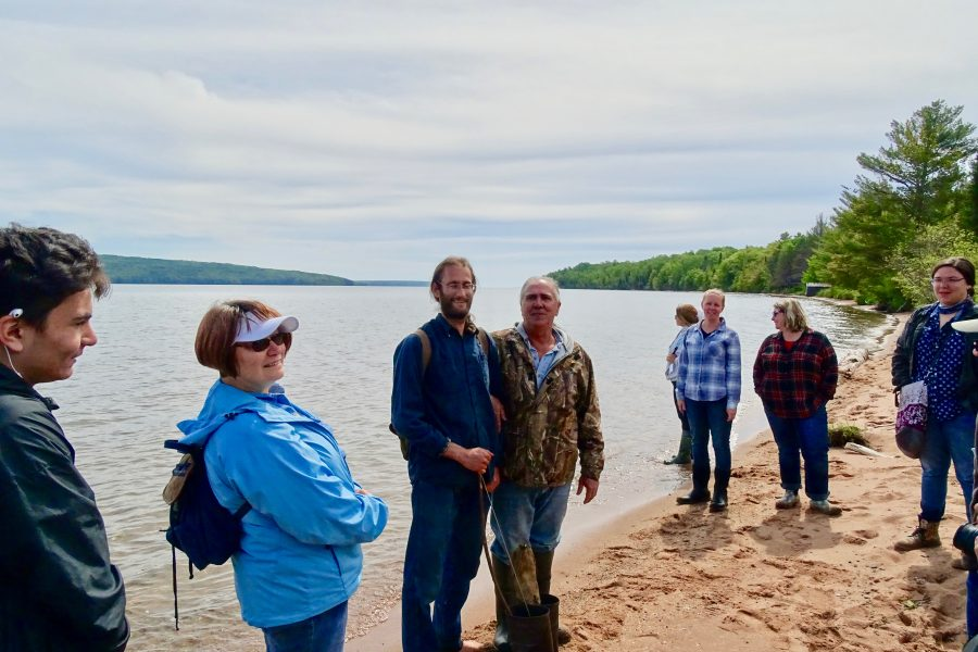 Six people stand on sandy shoreline of Lake Superior, smiling.