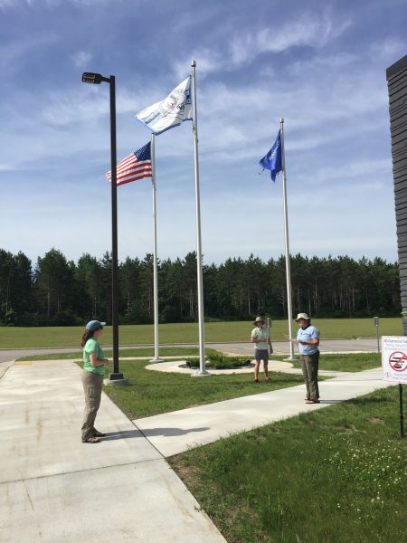 The flags of the United States of America, the Ho-Chunk Nation, and the state of Wisconsin all fly in front of the District One Community Center.