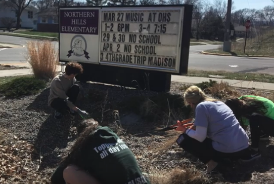 children kneel to plant in rain garden area in front of elementary school sign