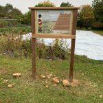 Sign describes purpose of prairie restoration adjacent to food pantry garden